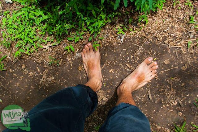 Melepas alas kaki demi kenyamanan pengunjung menuju Air Terjun Coban Talun di Kota Batu