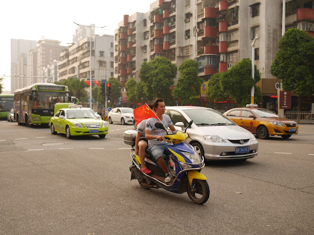 man riding a scooter with a PRC flag in Zhongshan, China