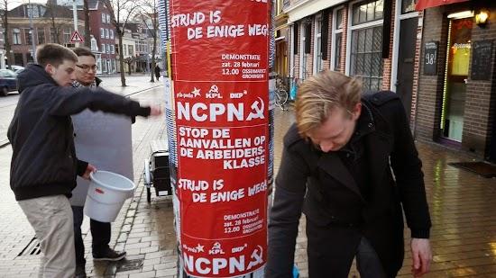 Genossen kleben Plakate.