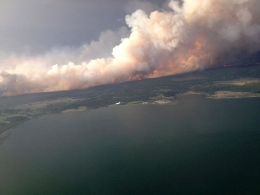 Smoke rises from a 7,000 hectare (17,000 acre) fire on the north side of Puntzi Lake, British Columbia in a picture release by the BC Wildfire Service 11 July 2015. Photo: BC Wildfire Service / REUTERS