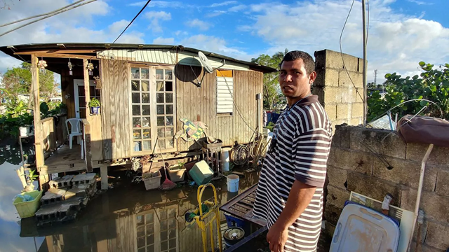 Yaniel Alexis Perez outside his flooded home in Añasco, Puerto Rico. He has not had electricity since Hurricane Maria hit in September 2017. Photo: Milton Carrero Galarza / The Los Angeles Times
