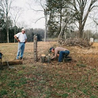 Using the chain saw to cut the tree stump closer to the ground.