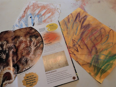 A book and a drawing showing cave paintings of hands