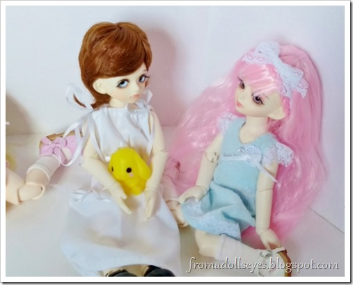 The pink haired bjd (Yuna) is saying something nice to the little boy bjd (Makoto).  Technically anything she says sounds nice to him because he really likes her.