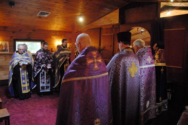 Clergy pray around the altar.