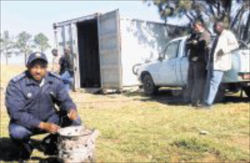 DEADLY GADGET: Captain Shado Mashobane with the brazier the tree dead men are believed to have taken into the container in which they slept. Pic. Len Kumalo. © Sowetan.