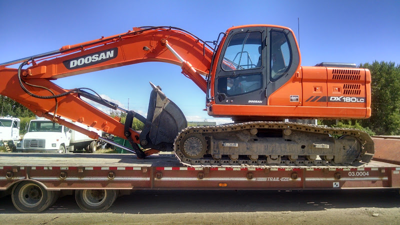 orange Doosan excavator loaded on flatbed trailer
