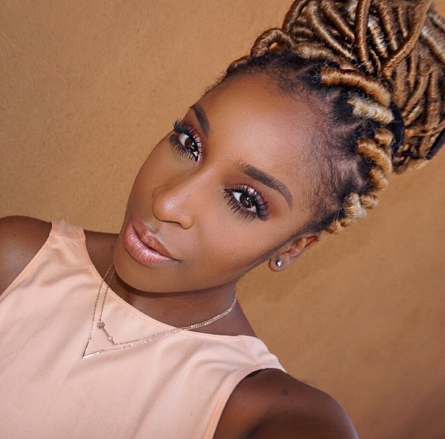 jackie aina with golden faux locs in her hair