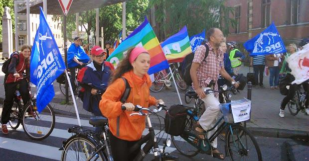 Radfahrerinnen und Radfahrer mit Friedensfahnen an den Rädern.