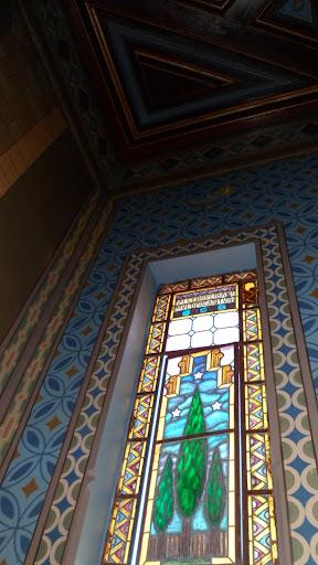 """Tem-se, no vitral esquerdo, a figura das Cédulas do Líbano. A frase em latim, na parte superior do vitral, inicia a informação que termina no vitral esquerdo: """"O justo se multiplicará como cédulas do Líbano""""."""
