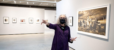 """Photo of Mary Anne Redding, curator at the Sioux City Art Center, while discussing the center's new exhibition, """"Magnetic West."""""""