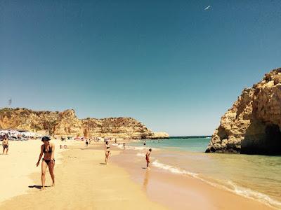 En mindre strand med en klippe ute i vannet og en ved enden av stranden.
