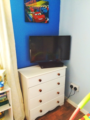 Corner of a childs room with white drawers and a tv