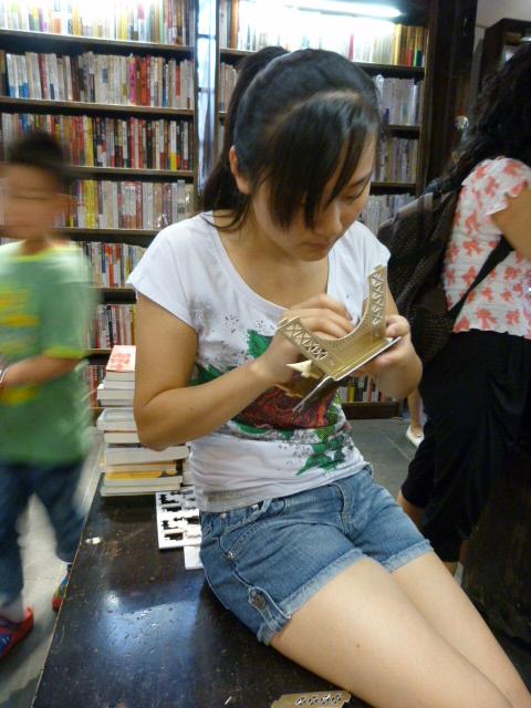 Cette vendeuse,dans une librairie assemble une tour Eiffel...