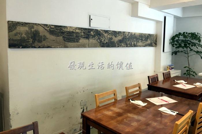 台北東湖【喜相逢麵館】內部裝潢一隅,基本上就是幾張桌子,然後牆壁上有一幅好像是清明上河圖的中國畫(沒仔細看)。