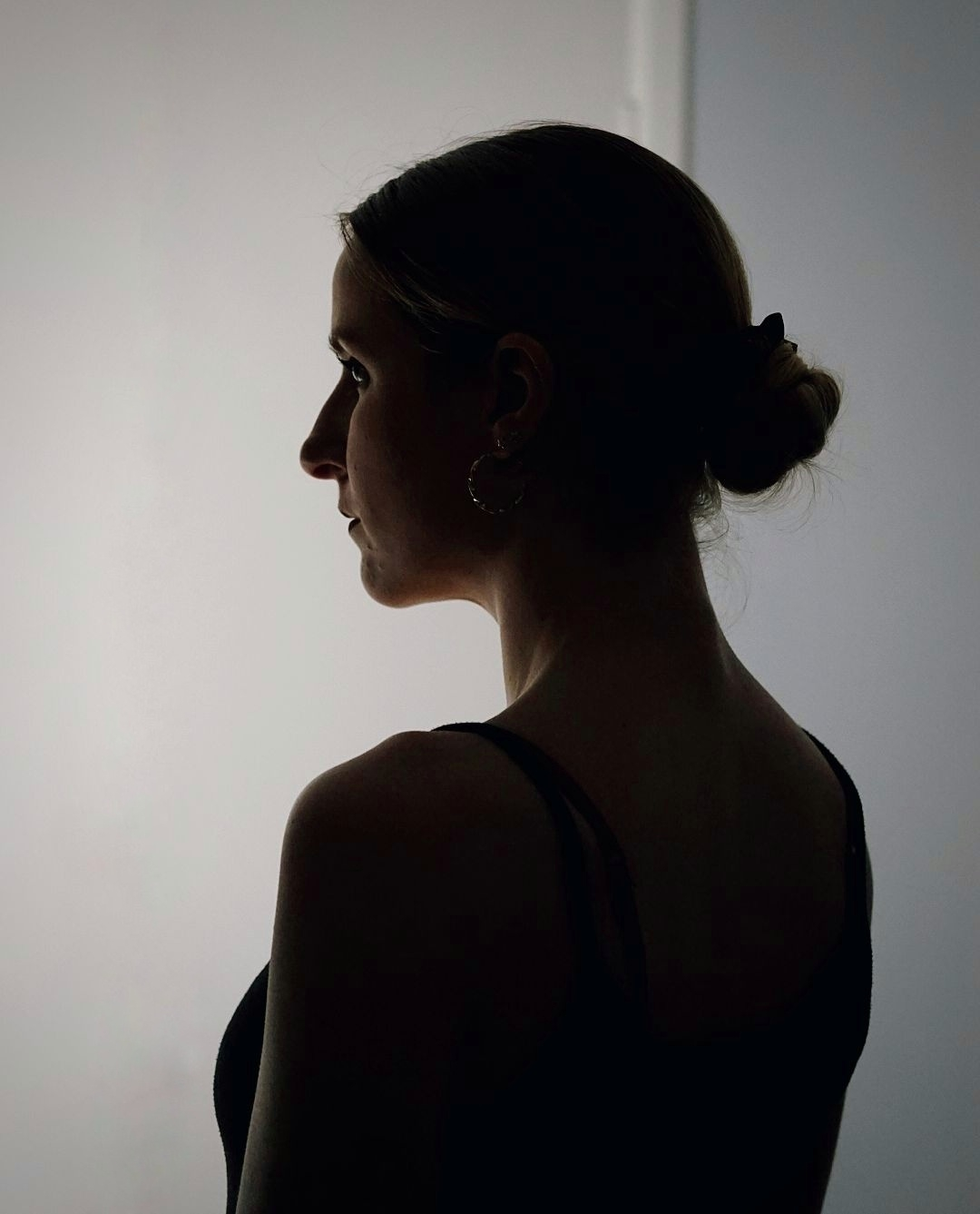 A silhouette of a woman in a black strappy top