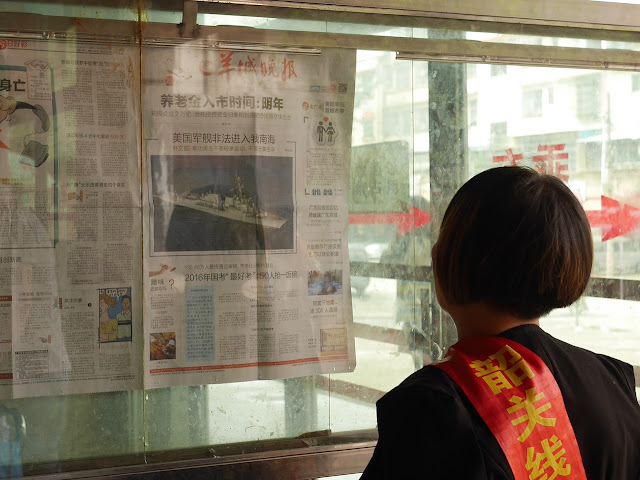 Woman at a bus station in Nanxiong, China, reading news about the U.S. challenging some of China's territorial claims in the South China Sea