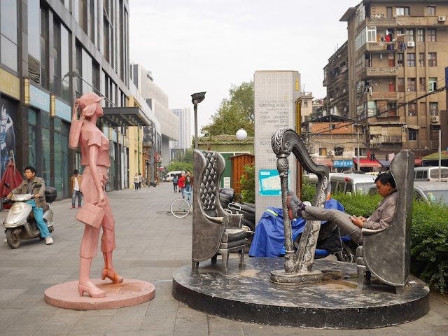 man looking at his mobile phone while sitting on a sculpture of chairs with a harp in Changsha