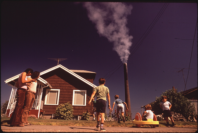 Children play in yard of Ruston Home, while Tacoma smelter stack showers area with arsenic and lead residue in 1972. Photo: Gene Daniels / National Archives