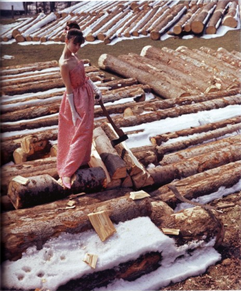 Audrey Hepburn is standing on some logs in the middle of a frozen snowy lumber yard.  Her shoulders are bare because she is wearing an elegant apricot evening gown, complete with satin slippers and elbow gloves.  Her hair is swept up into a complicated hairdo and held back with something shiny.  In her left hand she is holding a traditional lumberjack axe resting gently against a log.