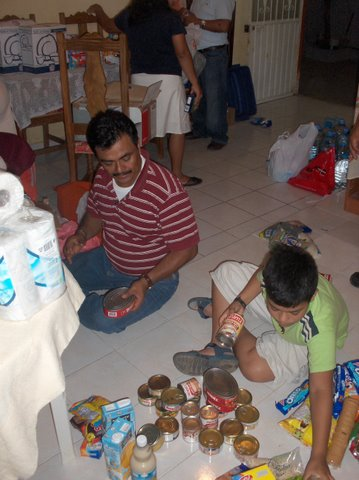 Pastor Ruben and his son Benjamin sort out supplies to be handed out the next day. In this home, which belonged to Pastor Ruben, the flood waters filled the first floor.