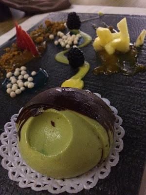 Grønn krem dekket av sjokolade. Frukt i bakgrunnen.