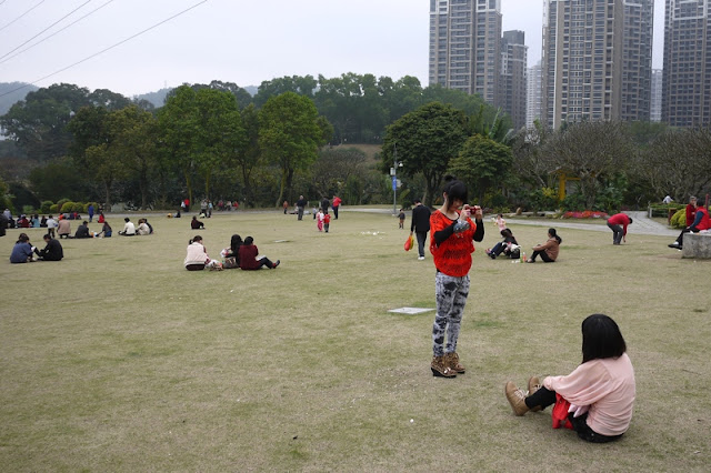 young woman taking a photo of another at Bailian Dong park in Zhuhai China