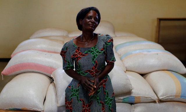 Subsistence farmer Salome Banda stands beside bags of her maize stacked in a warehouse north of Lilongwe, Malawi. Photo: Reuters