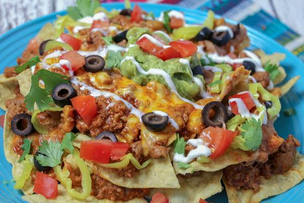 Working Mom's Layered Nachos On A Plate Sprinkled With Olives, Tomatoes, And Cilantro.
