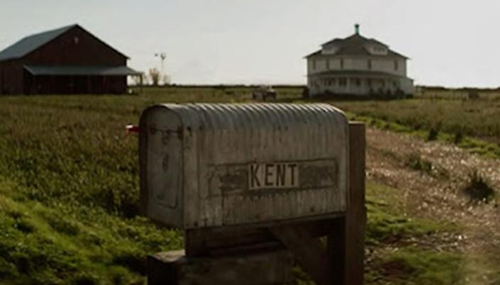 """Caixa de correio antiga escrito """"Kent"""" e ao fundo a fazenda com a casa e o celeiro."""