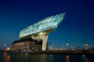 futuristisch gebouw in vorm van een schip 'vaart' over oud Havengebouw