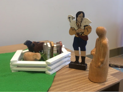 "Flat wooden figures mounted on bases to stand upright: A male figure carrying a lamb on his shoulders, and five sheep enclosed by a wooden toy fence. Also within the fence is a wooden sheep from a nativity set, and next to the ""Good Shepherd"" is the shepherd from a nativity set."