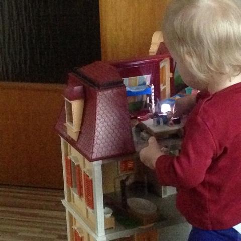 Kind spielt mit dem Puppenhaus