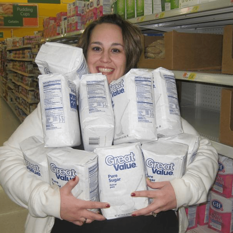 Volunteer holding bags of sugar