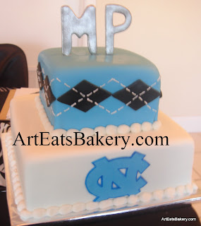 Two tier square blue, white and black men's creative custom University of North Carolina logo birthday cake design with silver monogram topper