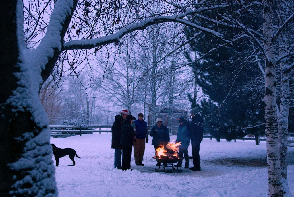 Friends warm up around a bonfire at the ranch.
