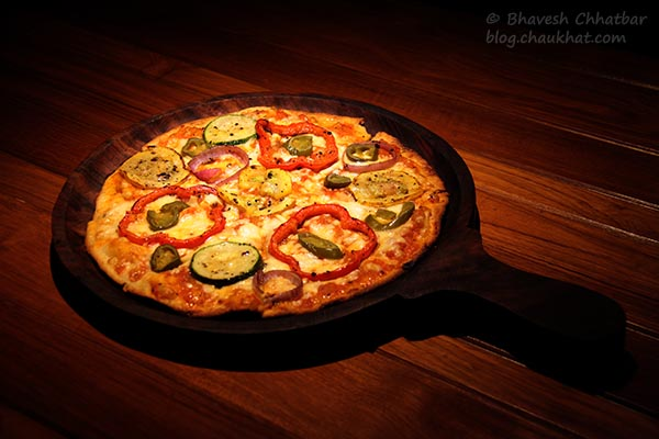 Close-up of Thin-crust Gourmet A La Toss Pizza served at Toss Sports Lounge Koregaon Park