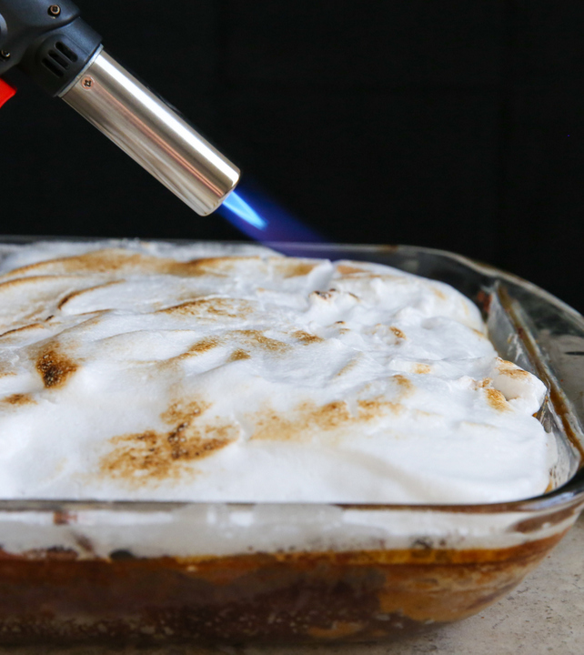 photo of a kitchen torch toasting the topping on the cake