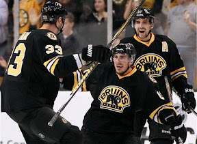 Brad Marchand celebrates his goal with Zdeno Chara and Patrice Bergeron