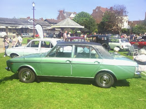 beautiful green classic saloon on grass field in amongst other classic cars at a show