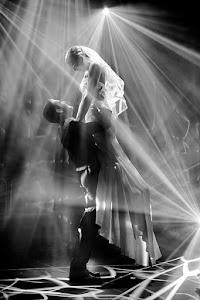 bruidegom tilt de bruid op omgeven door stralend licht