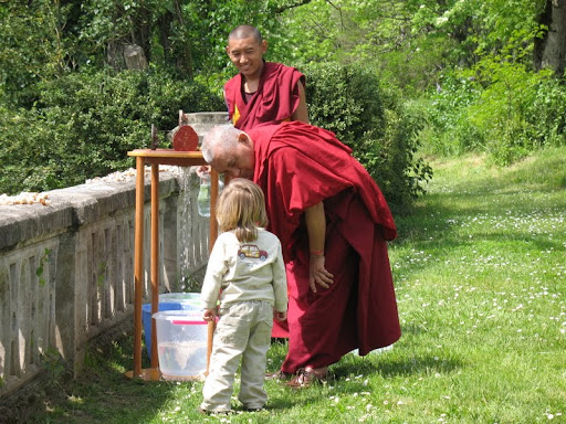 Lama Zopa Rinpoche being helped with small friend while doing water charity practice at Nalanda Monastery, France