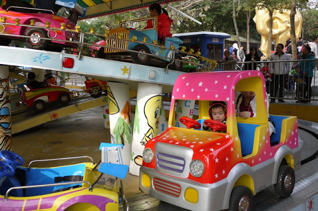 Child on kiddy-car amusement park ride in Zhuhai, China