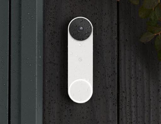 Une Nest Doorbell est installée sur la façade d'une maison. Elle est couverte de gouttelettes de pluie. On peut apercevoir dans le cadre un doigt qui appuie sur la sonnette.
