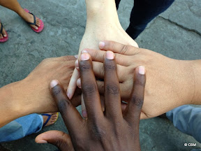 Four hands interlinked in a show of unity