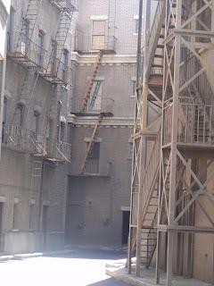 Trangt smug mellom murbygninger med flere branntrapper.