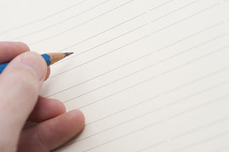 Photo: Male hand holding a pencil ready to commence writing on a blank lined sheet of paper