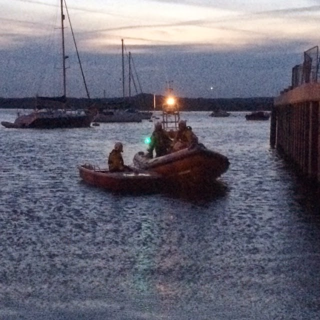 Poole ILB crew bringing a small tender ashore after it was stuck on the mud with another vessel and six people in the fading light on Friday 6 June 2014 Photo: RNLI Poole/Paul Taylor