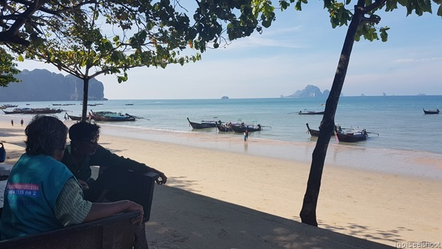 Boatman and passengers relaxing under the shade by Ao Nang beach. The steep cliffs of Railay Peninsula could be seen in the background on the left of photo.