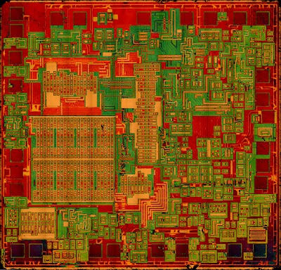 Die photo of the 76477 sound chip. The metal layer has been dissolved with acid to reveal the silicon. Colors are enhanced. Photo courtesy of Sean Riddle.